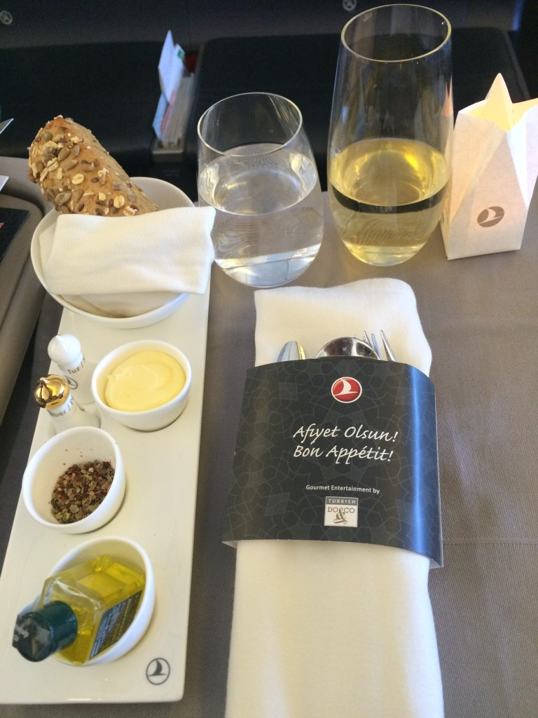 The meal service begins. There is no meal tray here, the table is entirely laid out before the passengers by the crew. Here is my table layout with cutlery, olive oil, spices, bread and butter. The electric tea candle adds a romantic touch.